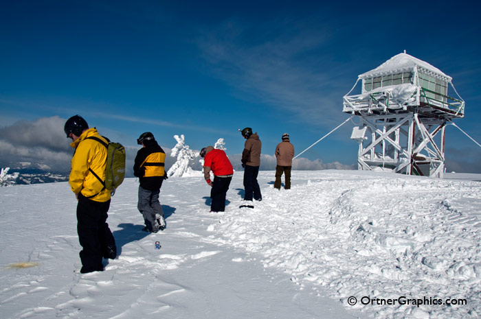Photo of men being on a snow covered mountain top.
