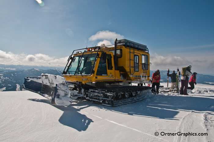 Photo of a snowcat and skiers and snowboarders on a mountaintop